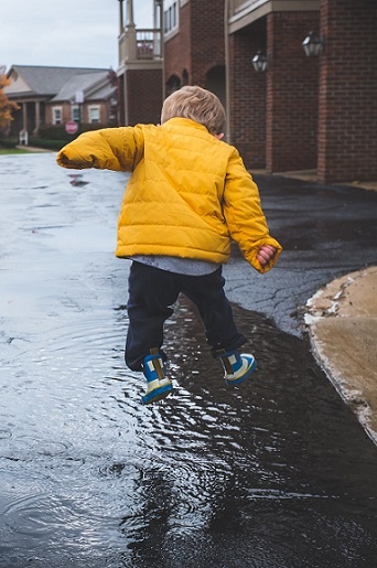 Child jumping in puddles. Photo by Neonbrand on Unsplash photo website.